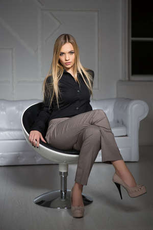Young attractive blonde wearing business clothes sitting on a chair