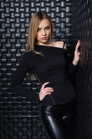 Portrait of cute young woman wearing black clothes posing in studio