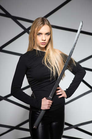 Portrait of charming blond woman posing with sword Stock Photo