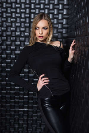 Portrait of sexy young woman wearing black clothes posing in studio