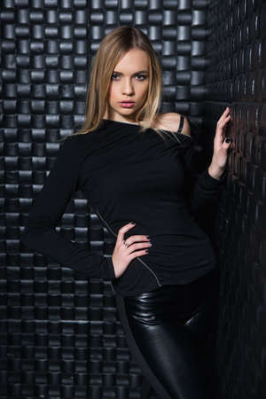 Portrait of inviting young woman wearing black clothes posing in studio