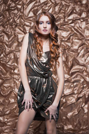 Portrait of sexy red-haired woman wearing glossy dress posing in the studio