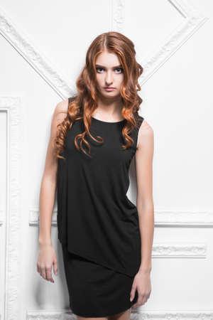 Portrait of elegant woman wearing black dress posing in the studio