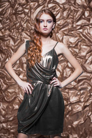 Portrait of pretty red-haired woman wearing glossy dress posing in the studio