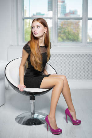 Thoughtful red-haired woman wearing black dress and pink shoes sitting in a chair Stock Photo