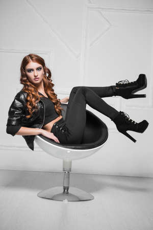 Playful red-haired lady wearing black fashionable clothes posing in a chair
