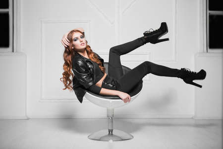 Leggy red-haired lady wearing black fashionable clothes posing in a chair