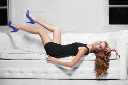 Sexy woman wearing black dress and blue shoes posing on the white sofa