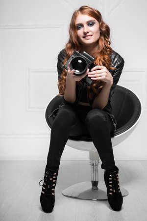 Smiling curly woman posing with camera in a chair