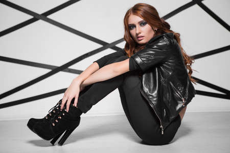 Sexy young woman wearing black fashionable clothes and high heels sitting on the floor