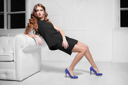 Charming red-haired woman wearing black dress and blue shoes posing near white sofa Stock Photo