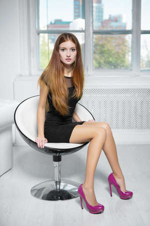 Beautiful red-haired woman wearing black dress and pink shoes sitting in a chair Stock Photo