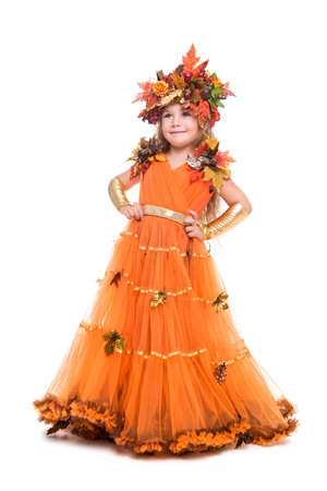 Smiling little girl wearing orange autumn dress and wreath. Isolated on white