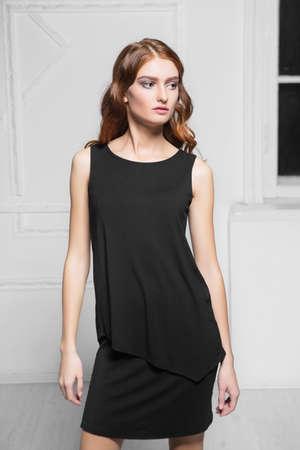 Portrait of thoughtful woman wearing black dress posing in the studio