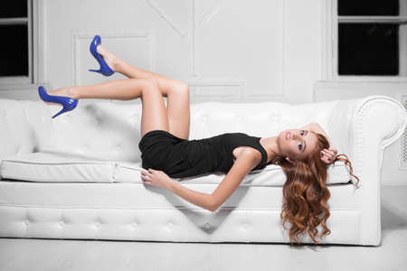 Attractive woman wearing black dress and blue shoes posing on the white sofa