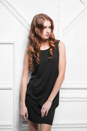 Portrait of pensive woman wearing black dress posing in the studio