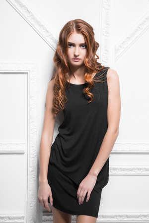 Portrait of beautiful woman wearing black dress posing in the studio