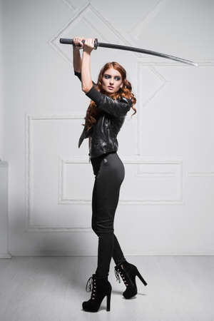 Sexy red-haired woman wearing black clothes posing with steel sword