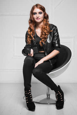 Cute red-haired woman posing with camera in a chair Stock Photo