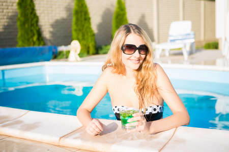 Portrait of cheerful blond woman posing in the swimming pool
