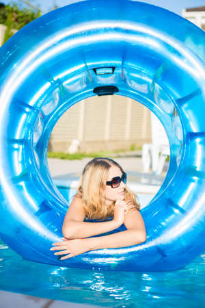Young blond woman posing with rubber ring in swimming pool