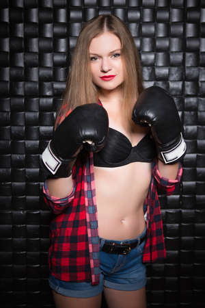 Young woman posing in checkered shirt and boxing gloves