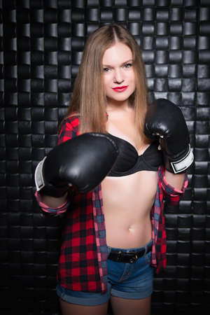Pretty blond woman posing in checkered shirt and boxing gloves
