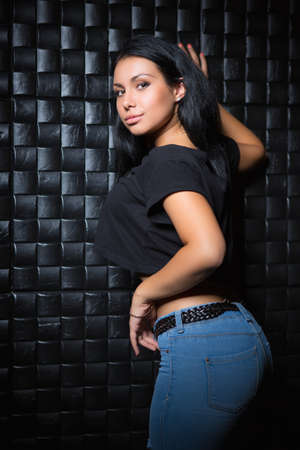 Young brunette wearing black t-shirt and blue jeans posing near the wall