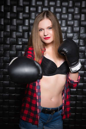 Young sexy woman posing in unbuttoned checkered shirt and boxing gloves