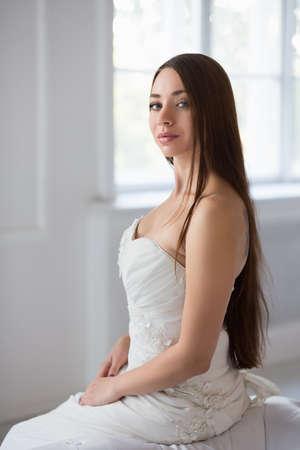 Portrait of beautiful brunette posing in wedding dress