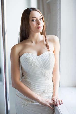 Portrait of attractive brunette posing in wedding dress