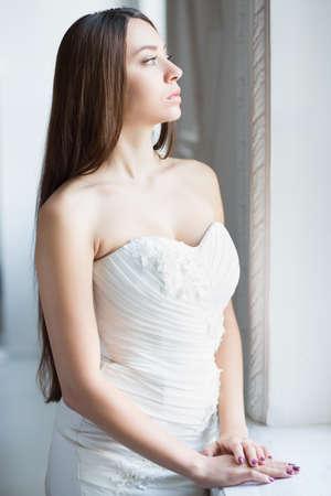 Portrait of pretty thoughtful brunette posing in wedding dress