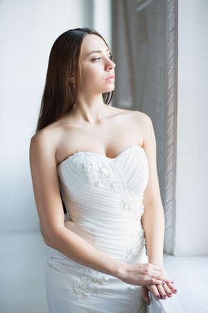 Portrait of nice thoughtful brunette wearing white wedding dress