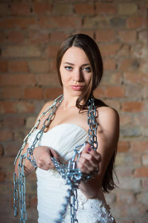 Portrait of playful brunette posing in wedding dress with chains