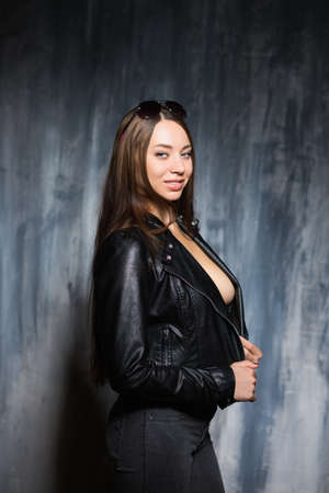 Portrait of sexy smiling brunette posing in black jacket and jeans