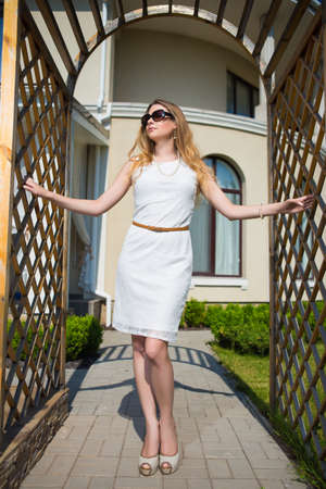 Attractive woman wearing white dress and sunglasses posing in archway Stock Photo