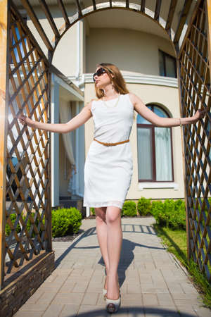 Beautiful blonde wearing white dress and sunglasses posing in archway outdoors Stock Photo