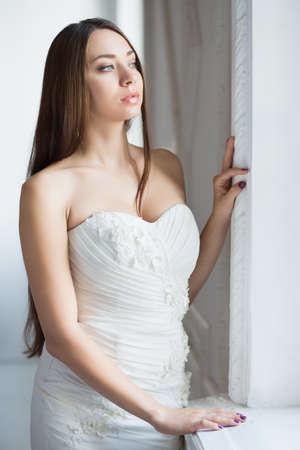 Portrait of thoughtful brunette wearing wedding dress