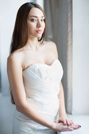 Portrait of attractive brunette wearing wedding dress