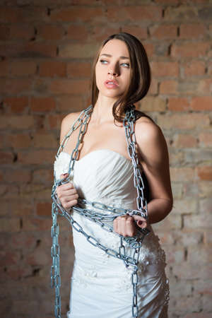 Portrait of young brunette posing in wedding dress with chains Stock Photo