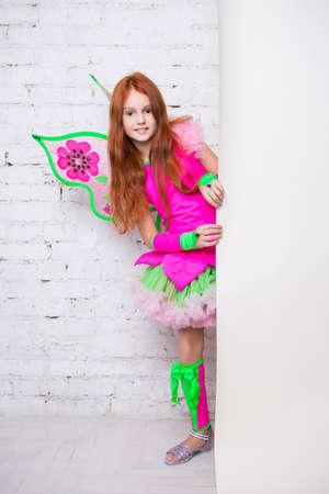 Beautiful little girl wearing pink butterfly costume posing near the wall