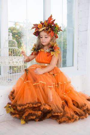 Attractive little girl wearing autumn costume posing near the window Stock Photo
