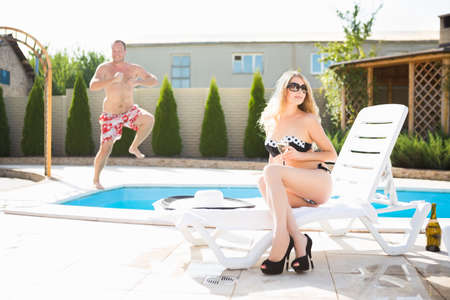 Young sexy blond woman and man posing near the pool Stock Photo