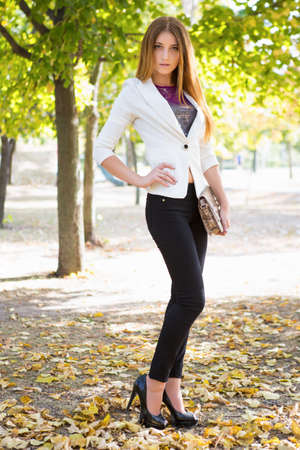 Portrait of a beautiful young brunette in autumn park