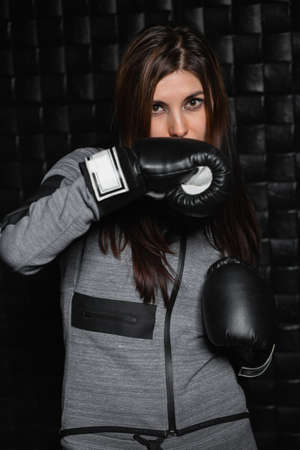 Portrait of a charming sporty brunette with boxing gloves near the black wall. Фото со стока