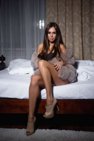 Sexy woman in fur vest sitting on the bed