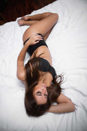 Slim beautiful brunette lying on the bed in lingerie