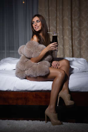 Playful sexy woman in fur vest and cocktail