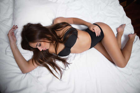 Portrait of a beautiful woman lying in black lingerie on a white bed Stock Photo