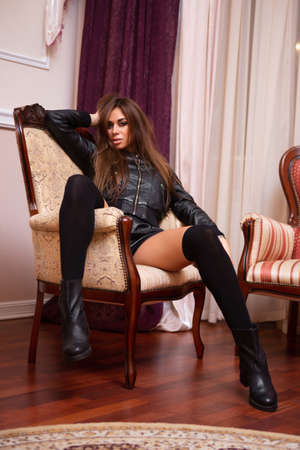 Sexy woman in black leather suit sits in an armchair